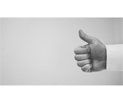 Black and white photgraph with a man in white shirt giving thumbs up