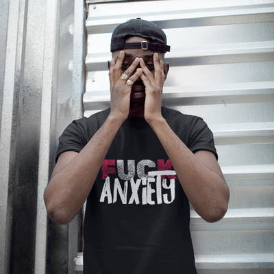 African american male with hands covering face wearing black tshirt saying Fuck anxiety