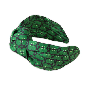 A Kate Whyley wide, knotted headband with a green and dark grey circle pattern, called Forest
