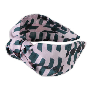 A Kate Whyley wide, knotted headband with a bottle green and blush pink pattern, called Peony