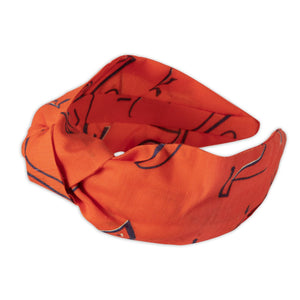 A Kate Whyley wide, knotted headband in tangerine orange, with black and white caligraphy-like design