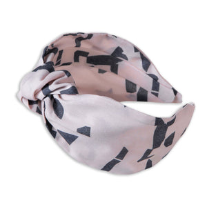 A Kate Whyley wide, knotted headband in blush pink and dark grey, called Direction
