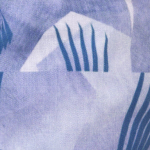 A close up image of Kate Whyley wide, knotted headband  cotton fabric, in blue hues, called Fan Flight