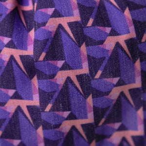 A close up image of Kate Whyley wide, knotted headband cotton fabric, with a purple and pink pattern, called Nitesky
