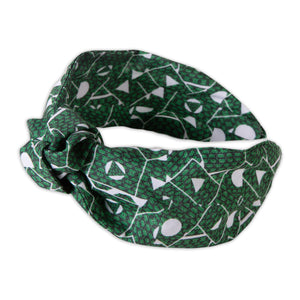 A Kate Whyley wide, knotted headband with a green and white pattern, called Topiary