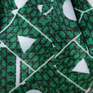 A close up image of Kate Whyley wide, knotted headband cotton fabric with a green and white pattern, called Topiary