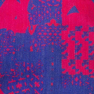 A close up image of the Kate Whyley wide, knotted headband cotton fabric - in cobalt blue and fuchsia pink design