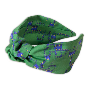 A Kate Whyley wide, knotted headband with a green, yellow and blue pattern, called Vert Amor