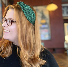 Load image into Gallery viewer, A auburn-haired woman wearing a Kate Whyley wide, knotted headband with a green and dark grey circle pattern, called Forest