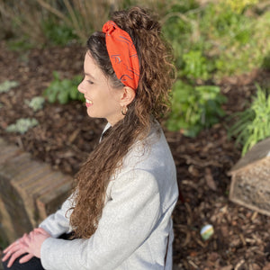 A brunette woman sitting on a wall, wearing a Kate Whyley wide, knotted headband in tangerine orange, with black and white caligraphy-like design