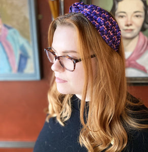 An auburn-haired woman wearing a Kate Whyley wide, knotted headband with a purple and pink pattern, called Nitesky