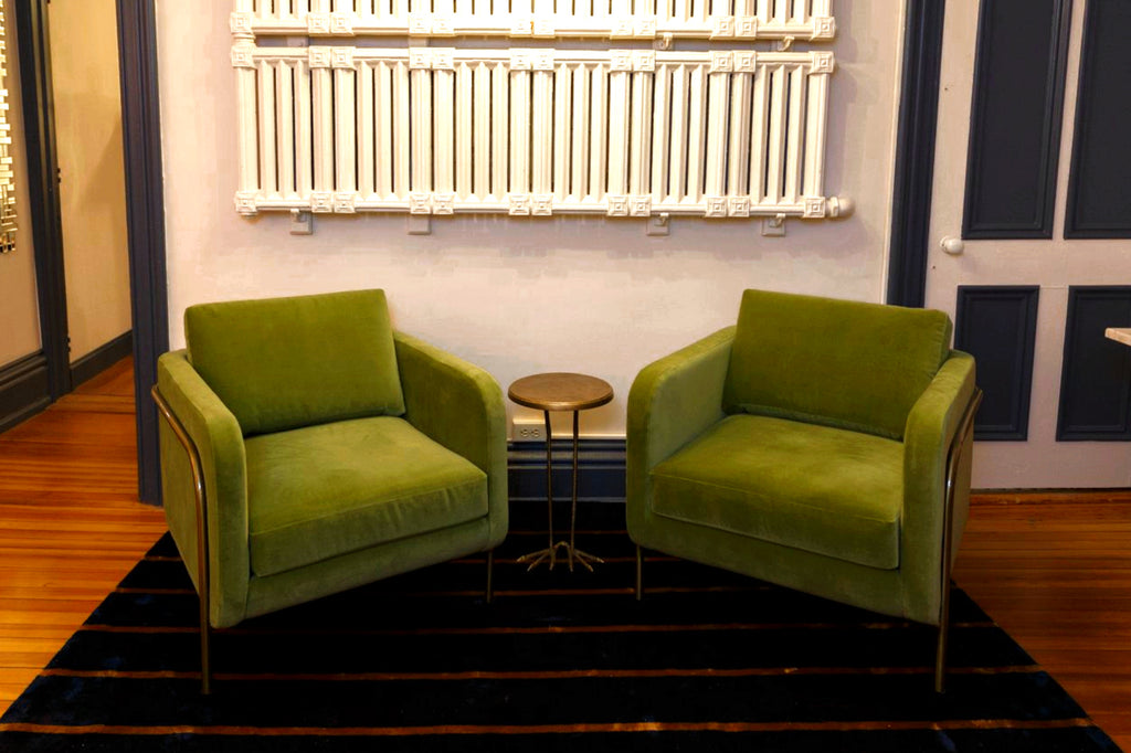 Green and brass commercial lounge chairs in coworking space