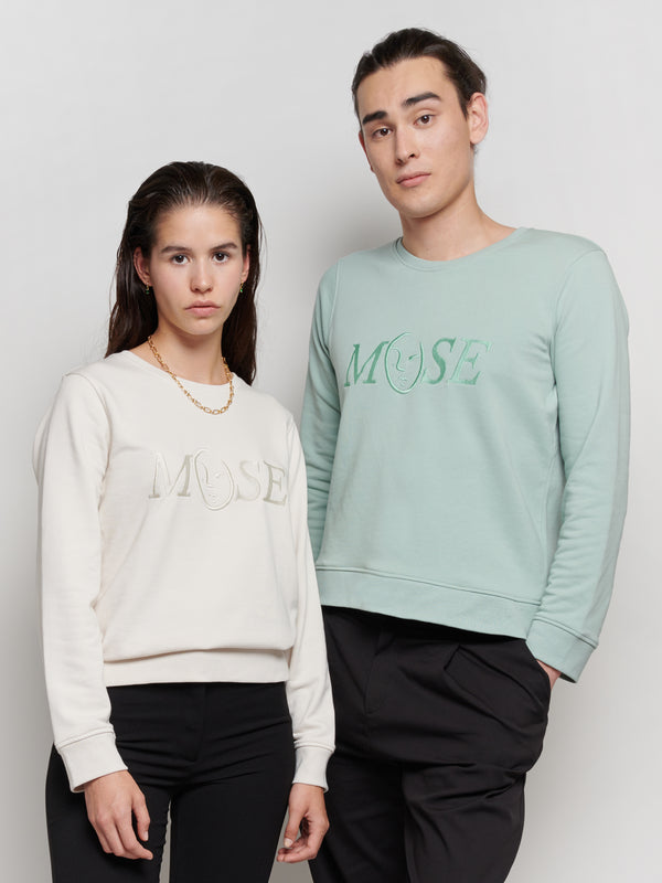 Our iconic Muse logo as a tone in tone embroidery for a vintage sweatshirt vibe. This sweater has a slightly cropped fit and is designed to be styled by men and women. The sweater is available in the colours off-white and sage green. It was locally designed in Luxembourg, the embroidery was made in Luxembourg and the sweater was proudly produced in Bangladesh with FairWear certification. The production of this item has been OEKO-TEX certified by OEKO-TEX.