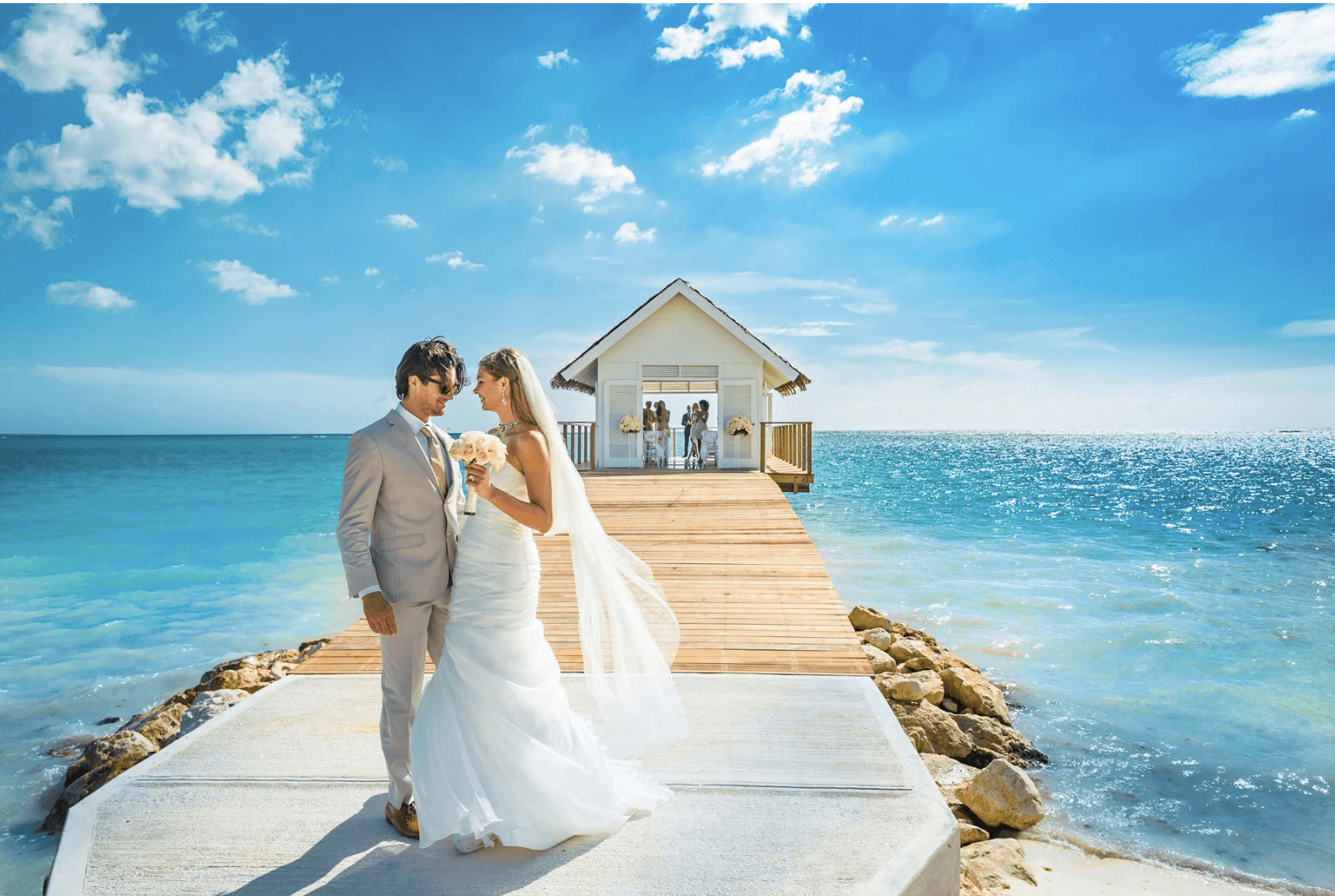 Bride and Groom stand on a pier with a chapel overlooking the clear blue ocean