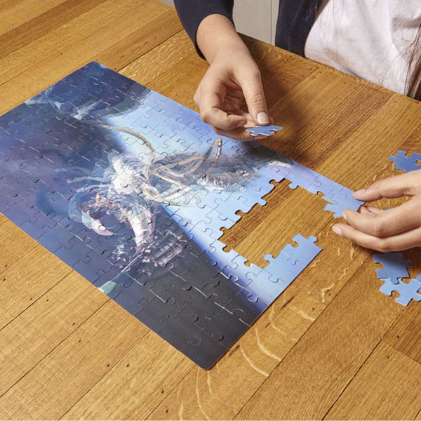 hands holding a jigsaw piece above a blue jigsaw on a brown table