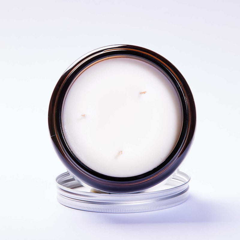 top of three wick candle with brown glass rim sitting on a metal screw top lid