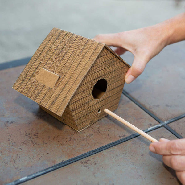 assembled cardboard birdhouse on top of tiled surface with hands inserting wooden dowel into hole in birdhouse