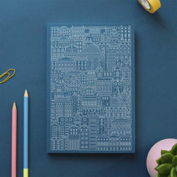 blue notebok with with line illustration of city buildings and brigdes on blue table with green plant, pink pencil, blue pencil, paper clip and yellow roll of tape