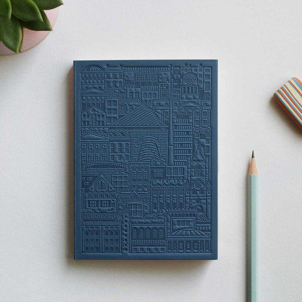 blue debossed notebook with city buildings, bridges and river on grey table with pencil, stripy eraser and plant in top left corner