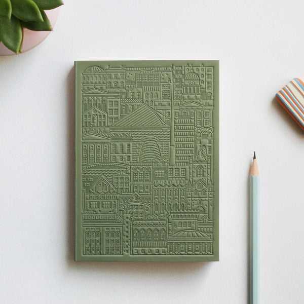 green debossed notebook with city buildings, bridges and river on grey table with pencil, stripy eraser and plant in top left corner