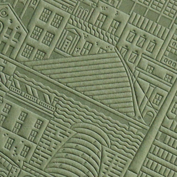 close up of green debossed image of a city bridge with buildings and water