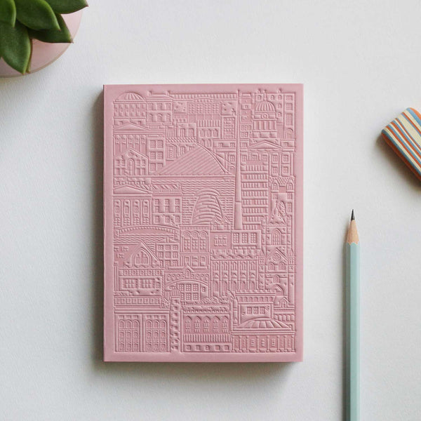 pink debossed notebook with city buildings, bridges and river on grey table with pencil, stripy eraser and plant in top left corner