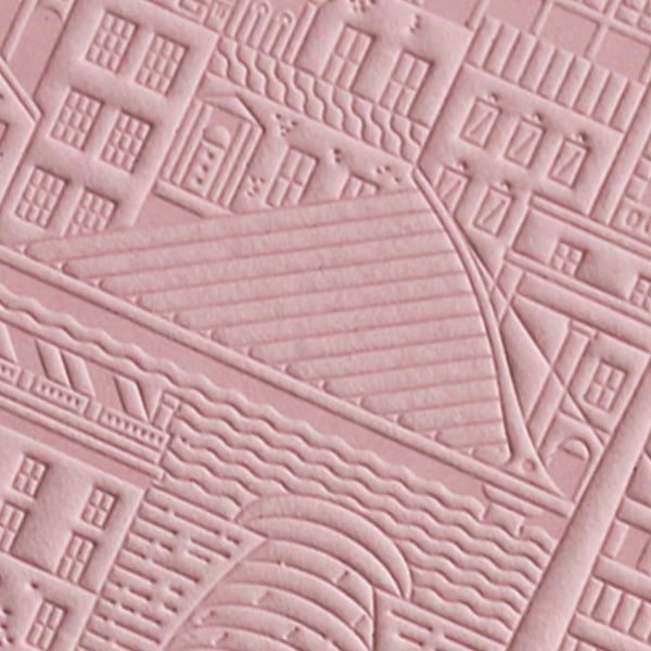 close up of pink debossed image of a city bridge with buildings and water
