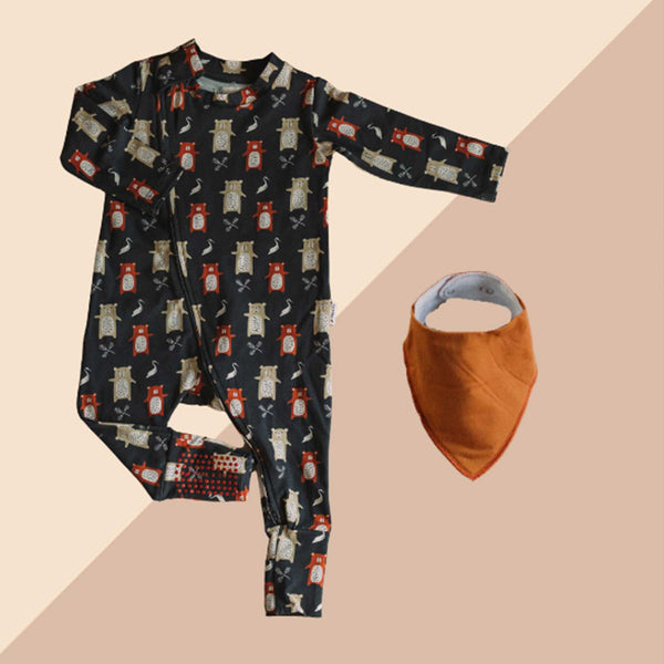 Baby sleepsuit dark grey with white red and brown pattern orange bandana bib against pink and taupe background
