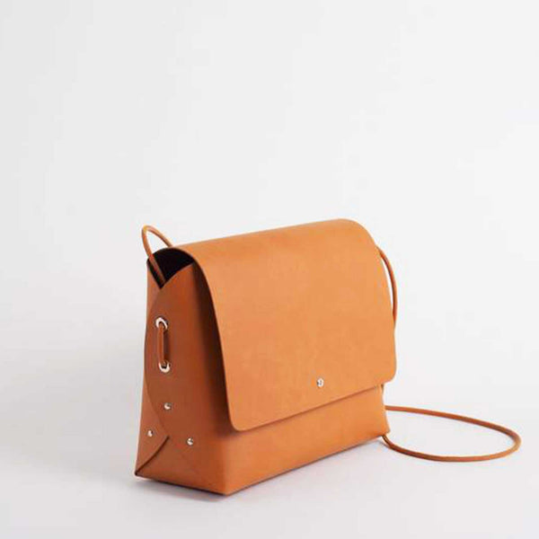 sideview of brick coloured handbag with three metal studs and looped cord on side and closed flap with metal button clasp