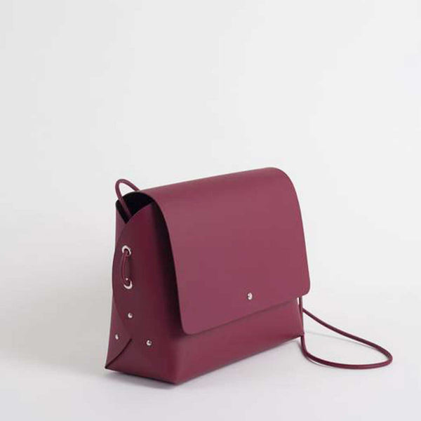 sideview of wine handbag with three metal studs and looped cord on side and closed flap with metal button clasp