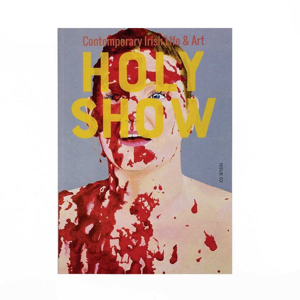 cover of magazine. a person from collarbones up with red splatter across their face and chest. The name of the magazine in yellow.