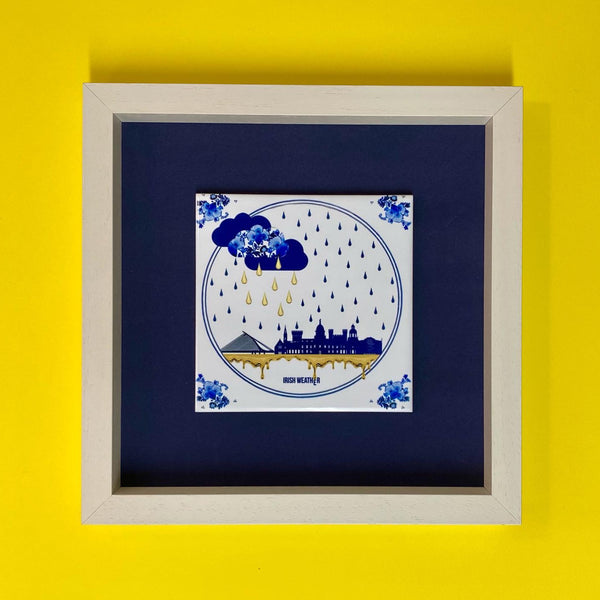 ceramic tile with navy blue dublin skyline , gold and navy blue raindrops and navy vlue clouds. behind the tile is a navy blue background and it is in a white frame. yellow display background