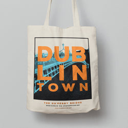 tote bag hanging.  tote has a design with of blue ha'penny bridge with white sky. orange text 'dublin town' over the image.