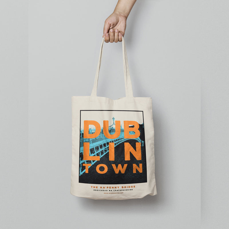hand hoding a hanging tote bag. tote has a design with of blue ha'penny bridge with white sky. orange text 'dublin town' over the image. white background.