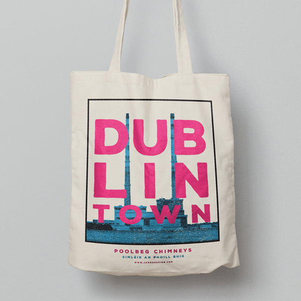 a tote bag hanging. the tote has a design of print of blue poolbeg chimneys with white sky. pink text 'dublin town' over the image. white background behind the tote