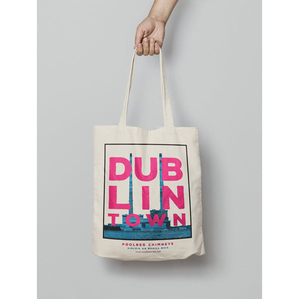 a hand holding a tote bag . the tote has a design of print of blue poolbeg chimneys with white sky. pink text 'dublin town' over the image. white background behind the tote
