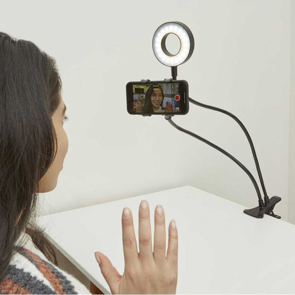 Girl waving to mobilee phone camera attached to a black live streaming kit with led ring light clipped to tabletop