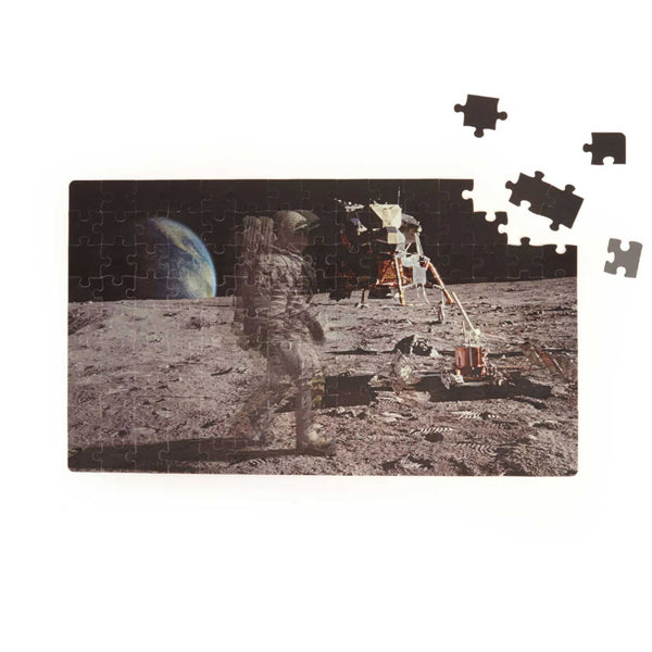 jigsaw of man on the moon with five unmade pieces
