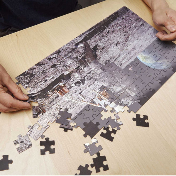 hands making a jigsaw of man on the moon on wooden table