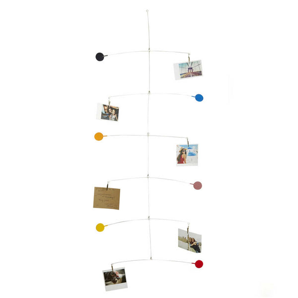 Steel wire mobile with six coloured circles  and five photographs and one brown paper note attached