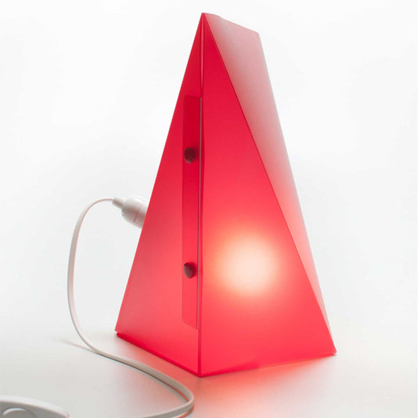 red triangle lamp with lit bulb inside two buttons on front and white cord attached on left side of lamp