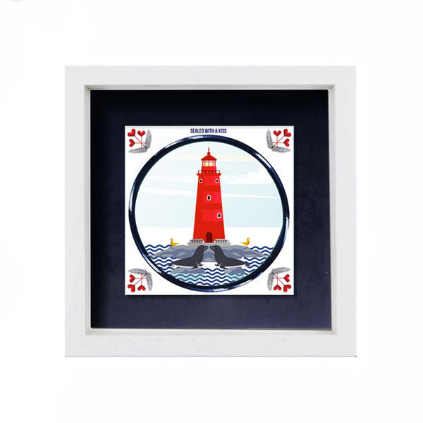ceramic tile with red lighthouse and two seals kissing in the sea in the foreground. behind the tile is a navy blue background and it is in a white frame. white display background