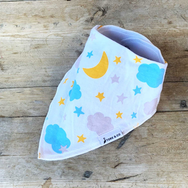 side view of closed white bandana bib with orange moon pink and blue clouds on wooden board