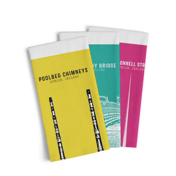 three tea towels on top of one another. the top one is yellow and  has a black image and text of poolbeg chimneys. the second is teal. the third is pink.
