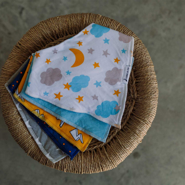 Stack of 5 bandana bibs on a wicker tabletop