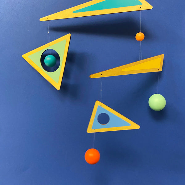 hanging mobile of multi tiered wooden triangles painted orange green blue and yellow and coloured balls attached by string with navy blue background