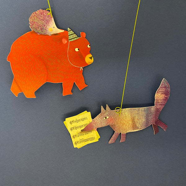 close up of animals on yellow strings. a brown bear with a party hat and hudgeboh on it's back and a purple fox with yellow sheet music. there is a navy blue background.