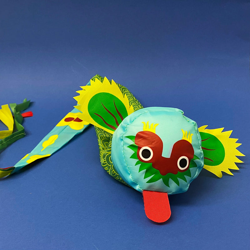 green blue and red fabric dragon throwing ball with green ears tongue sticking out and long tail on a navy background