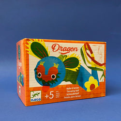product box on a navy background. the box is orange and white with the text 'dragon', 'throwing ball' and '+5'. image of product; green blue and red fabric dragon throwing ball with green ears tongue sticking out and long tail