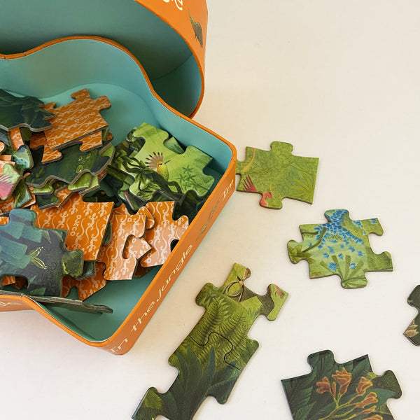 close up of box open with jigsaw pieces scattered on a white backhround. the pieces have jungle imagery.